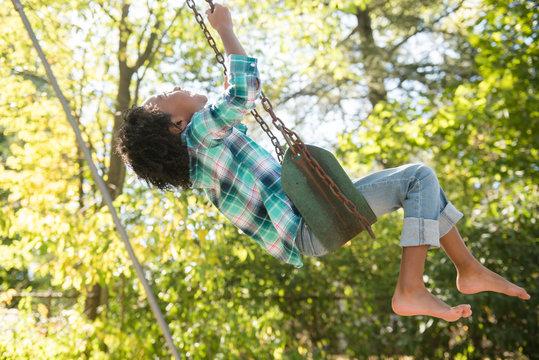 Girl swinging barefoot on swing