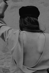 black and white portrait of stylish girl in the cap with a bare back