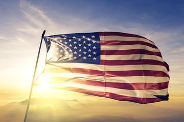 United States US american USA flag textile cloth fabric waving on the top sunrise mist fog