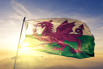 Wales welsh flag textile cloth fabric waving on the top sunrise mist fog