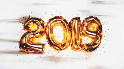 Bright metallic gold balloons figures 2019, Christmas, New Year Balloon with glitter stars on dark wood table background