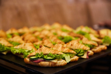 sandwiches, croissants stuffed with meat, cucumber, cheese and greens - buffet, Swiss table, blurred background