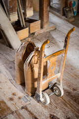 Vintage hand barrow standing upright on wooden floor, in flour mill, with two large bags of flour in front, Floor is white from flour dust