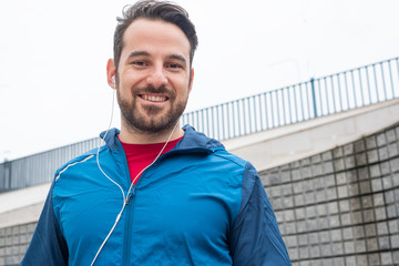 Runner sportsman holding mobile phone during workout