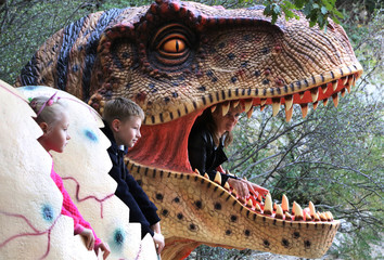 People pose for a photo during a dinosaur exhibition at the Nikitsky Botanical Garden outside Yalta