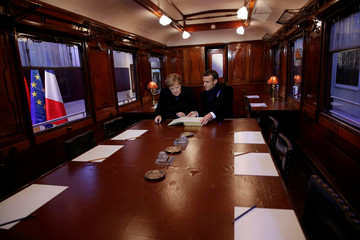 French President Emmanuel Macron and German Chancellor Angela Merkel sign a guest book inside a replica of the wagon where the Armistice was signed in 1918, in the Clairiere of Rethondes