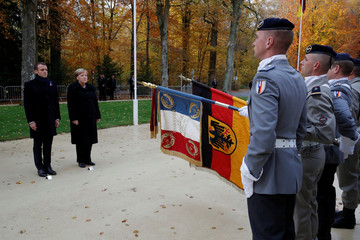 French President Emmanuel Macron and German Chancellor Angela Merkel review troops in the Clairiere of Rethondes