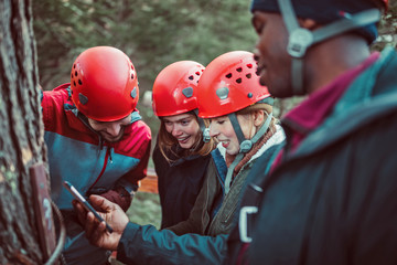 Friends gather around a phone to look at photos of them zip lining through the woods