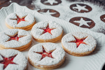 Powdered sugar marks and Linzer cookies on a plate