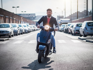 Young stylish man in suit and sunglasses driving scooter on empty road in sunny city.