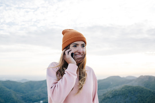 Smiling woman talking on smartphone?in mountains