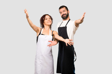 Couple of cooks presenting and inviting to come. Happy that you came on grey background