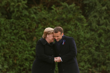 French President Emmanuel Macron and German Chancellor Angela Merkel hold hands after unveiling a plaque in the Clairiere of Rethondes during a commemoration ceremony for Armistice Day, 100 years after the end of the First World War, in Compiegne