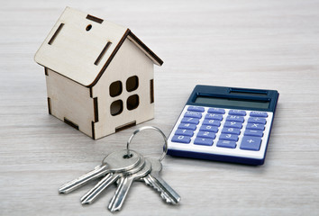 wooden miniature house with door keys and a calculator