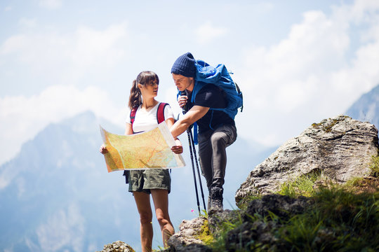 Backpackers using paper map in nature