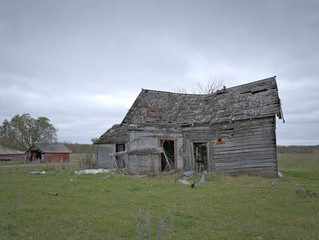 Dreary Abandoned Dilapidated Farm House with cloud skies in northern Minnesota