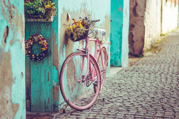 Foto op Canvas Fiets Pink vintage bike with basket full of flowers next to an old cyan building in Spain