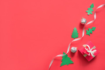 Christmas composition, mockup on red background. Christmas white and silver ribbon, gift box, garlands, toys border with copy space. Flat lay, top view