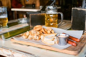 Glasses of light beer on pub background. Pint glass of golden beer with snacks and grill food on wooden table in pub, bar