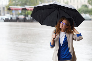 Young stylish woman with umbrella taking walk in the rain on summer day