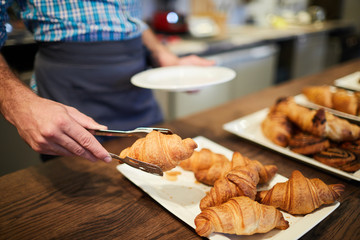 Waiter or sales clerk putting one of crusty croissants on plate for client of cafe