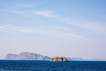 A small, rocky island juts out of a beautiful blue sea, in the Aegean Sea, near the Greek Island of Hydra.