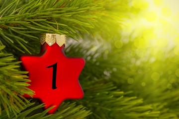 ein Weihnachtsbaumanhänger (Stern) am Baum mit einer Zahl (1) Wall mural