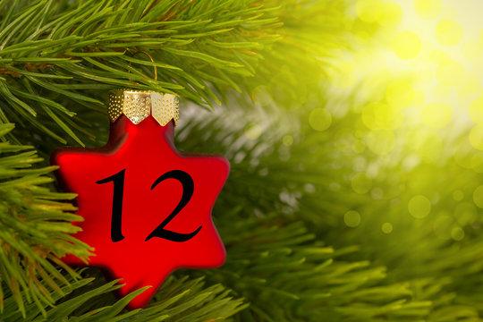 ein Weihnachtsbaumanhänger (Stern) am Baum mit einer Zahl (12)