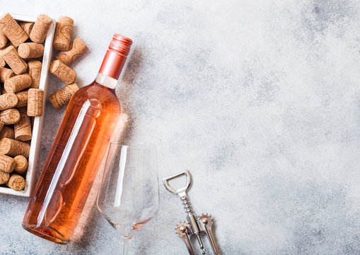 Bottle and glasses of pink rose wine with box of corks and corkscrew opener on stone kitchen table background. Top view. Space for text
