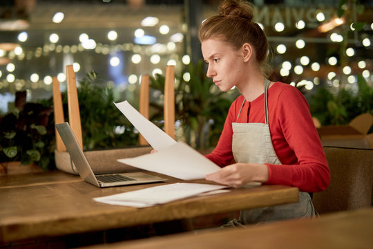 Serious young waitress in workwear sitting by table in front of laptop and reading papers