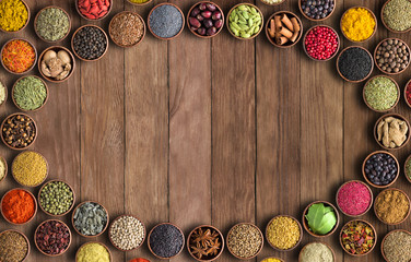 Fototapete - Spices and herbs on wooden table background. Frame of colorful seasonings, top view