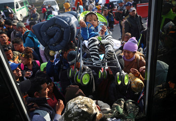 Migrants, part of a caravan of thousands traveling from Central America en route to the United States, make their way to Queretaro from Mexico City