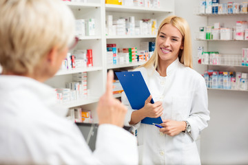 Mature and young female pharmacists working together, standing behind the counter. Young woman is holding a clipboard while her older colleague explains. Pharmaceutics and healthcare concept