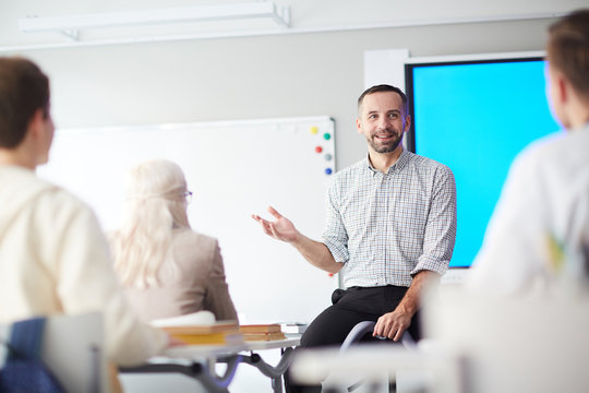 Happy confident teacher explaining his students what he thinks about new subject