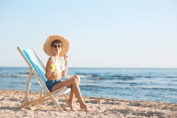 Young woman with cocktail in beach chair at seacoast. Space for text