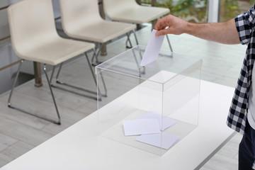 Man putting his vote into ballot box at polling station, closeup