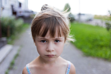 Close-up portrait of pretty young little blond pale unhappy moody friendless child girl looking sadly in camera on blurred sunny outdoors background. Children problems concept.