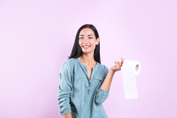 Beautiful woman holding toilet paper roll on color background