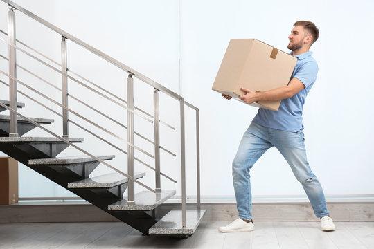Young man carrying carton box indoors. Posture concept