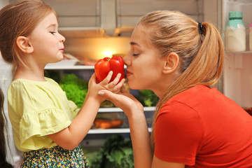 Young mother and daughter with fresh bell pepper near refrigerator at home