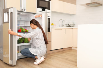 Young woman choosing products from refrigerator in kitchen