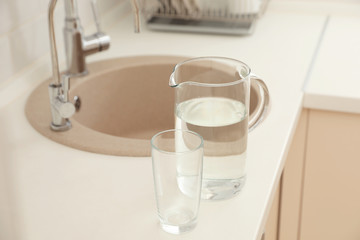 Jug and glass with water on table in kitchen