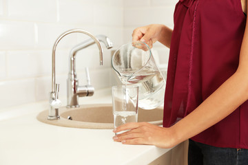 Woman pouring water from jug into glass in kitchen, closeup