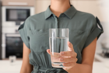 Woman holding glass with pure water in kitchen, closeup