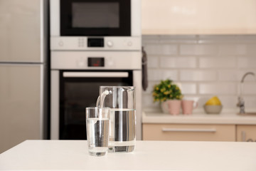 Jug and glass with water on table in kitchen. Space for text