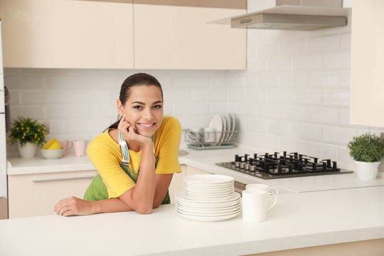 Beautiful young woman with clean dishes and cups at table in kitchen