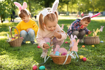 Cute little children hunting eggs in park. Easter tradition Wall mural
