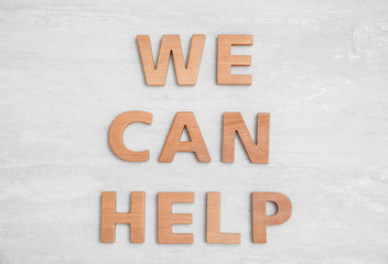 Text We Can Help made of letters on wooden background