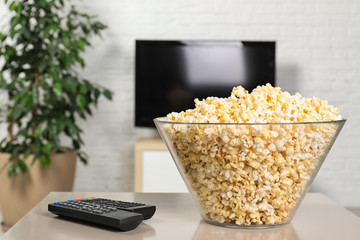 Popcorn and TV remote controls on table in living room