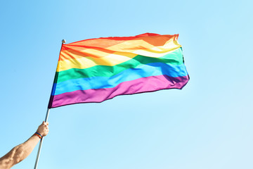 Gay man holding rainbow LGBT flag on blue sky background